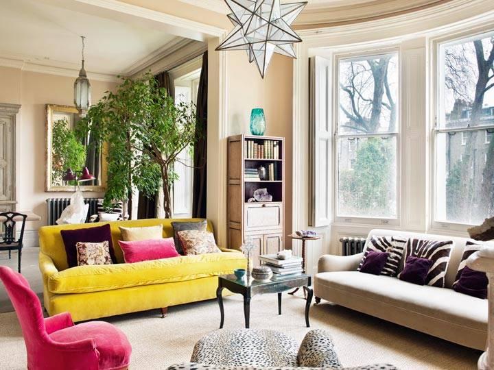 желтый диван и розовое кресло в комнате с эркером