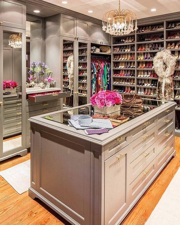 красивая гардеробная комната со столом и полками для обуви