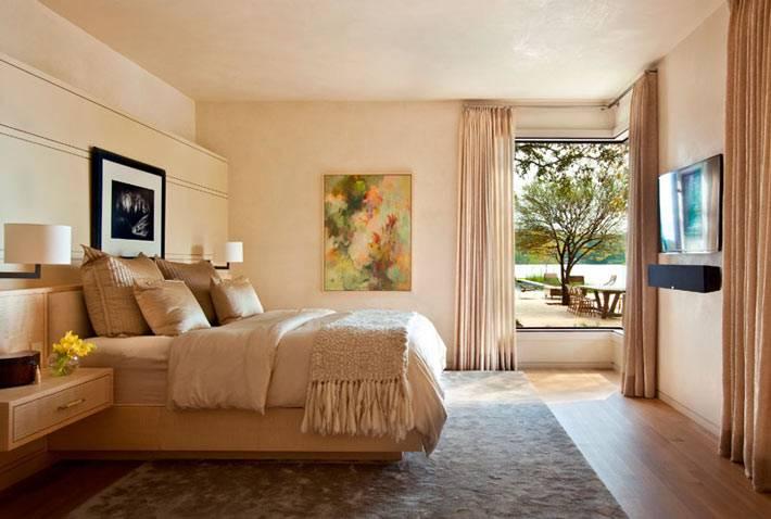 уютный интерьер спальной комнаты с видом на озеро
