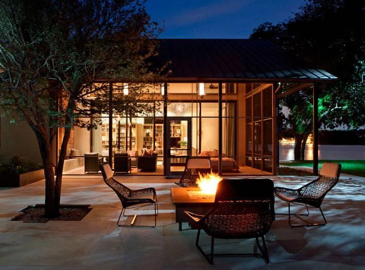 романтика вечерних посиделок возле костра у красивого дома