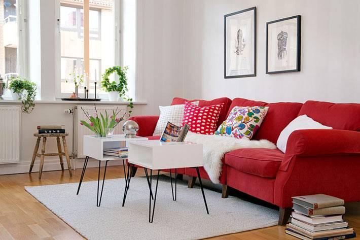 красный диван в интерьере белой гостиной комнаты
