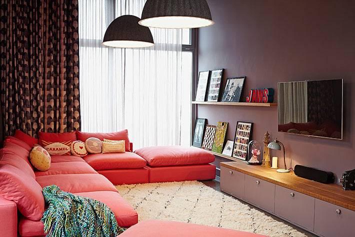 уютный интерьер гостиной с красным диваном