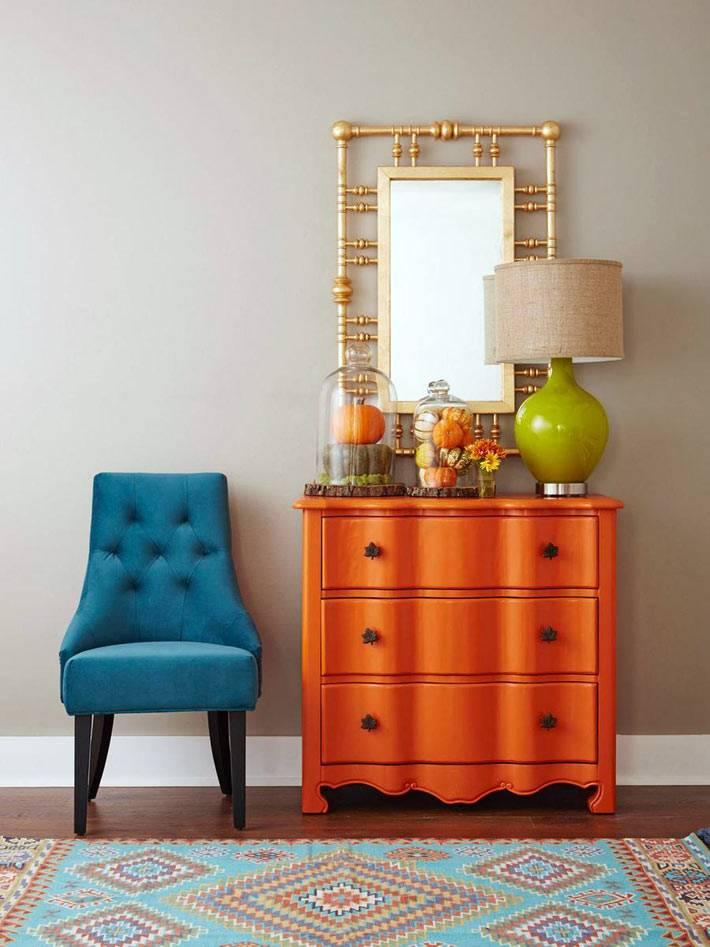 яркий оранжевый комод и синий стул в интерьере