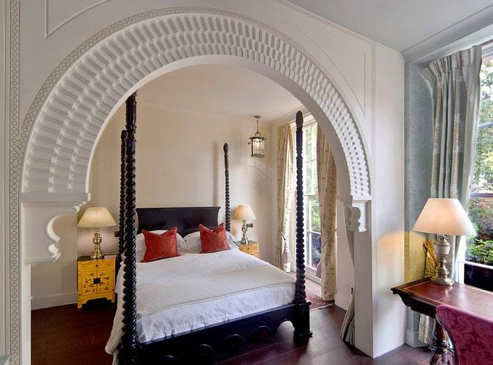 спальня с аркой и золотистыми тумбами