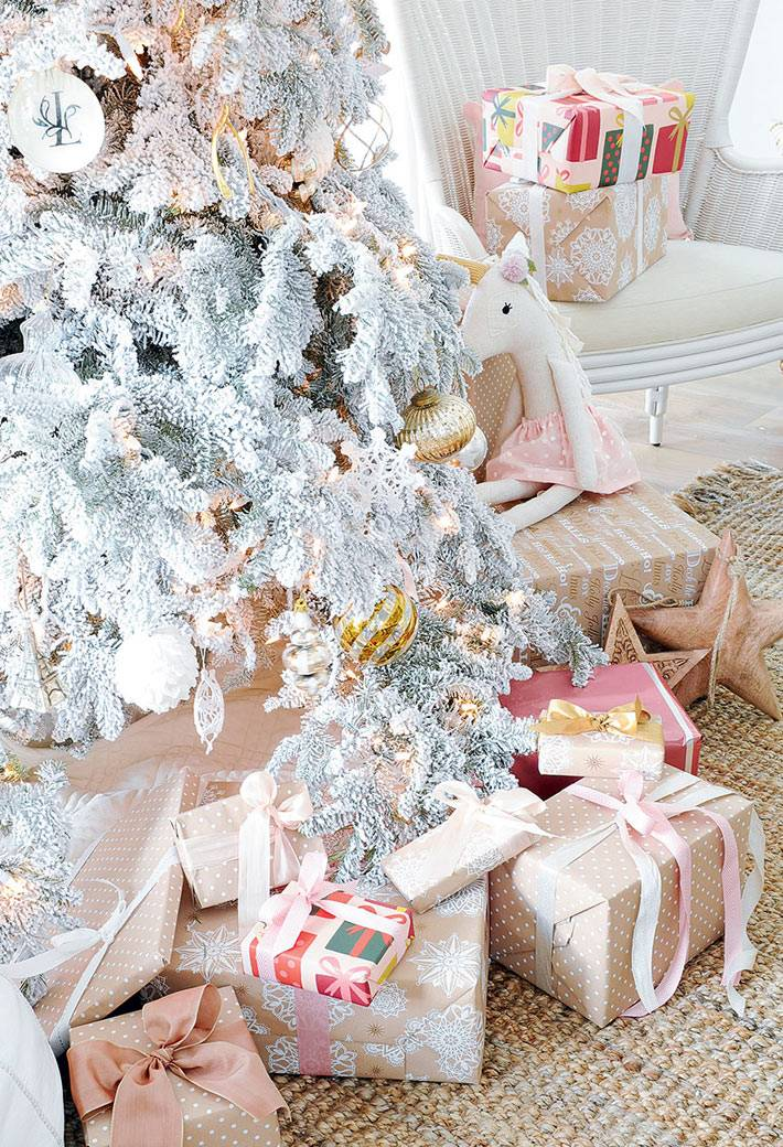 новогодние подарки под белой елкой в интерьере