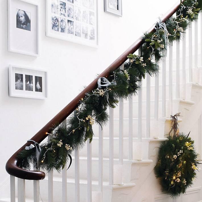 хвоя и гирлянды на перилах лестницы в новогоднем декоре