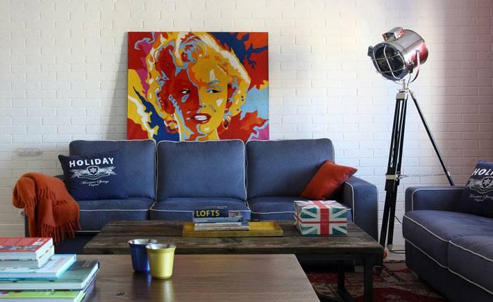 прожектор на триноге в интерьере красочной гостиной фото