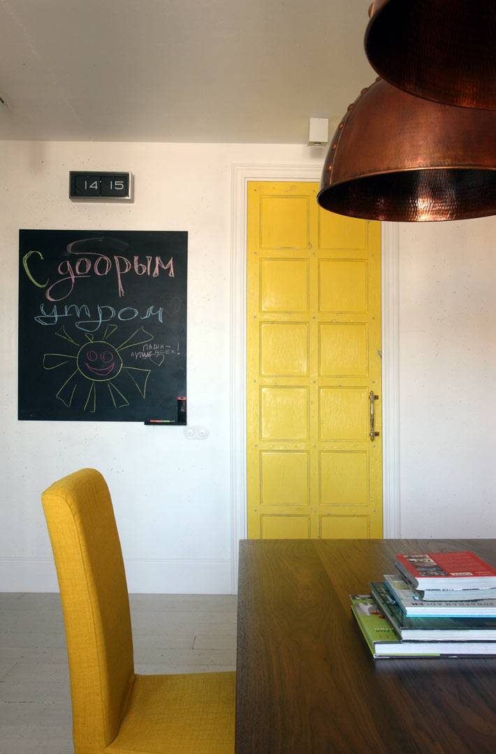 желтая дверь и меловая доска в гостиной комнате квартиры фото