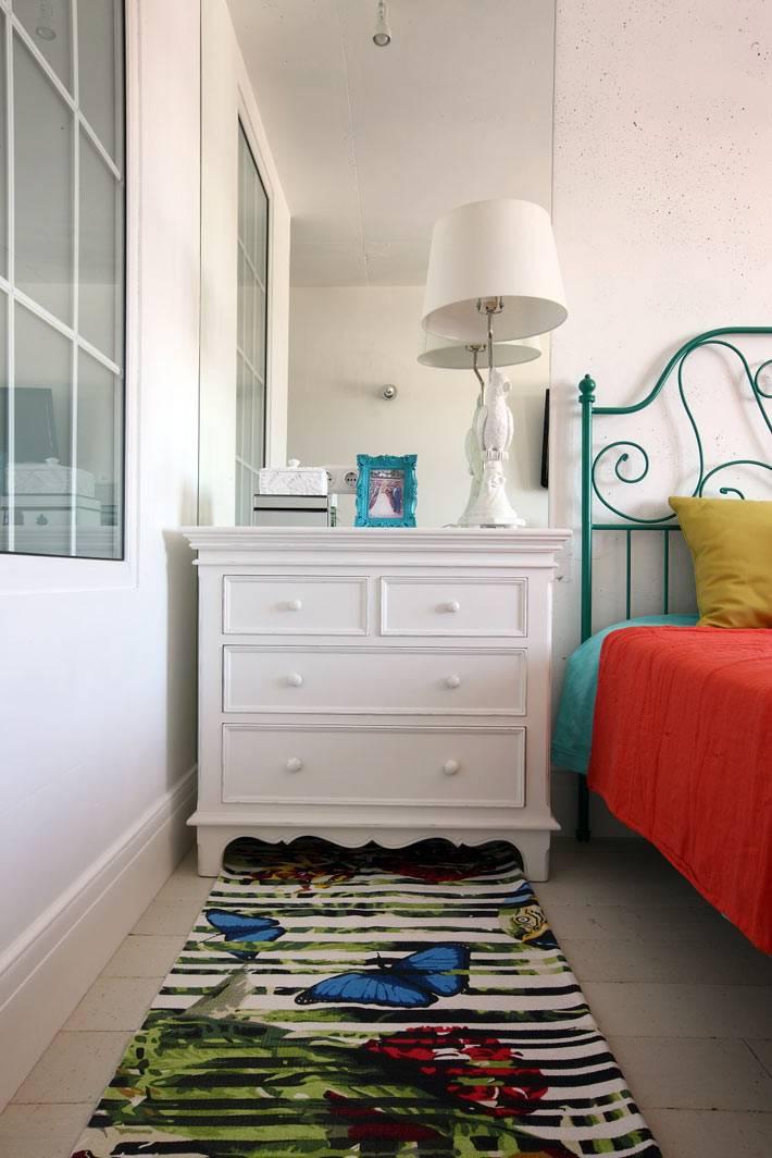 Белый комод и красивый придиванный коврик в интерьере спальни