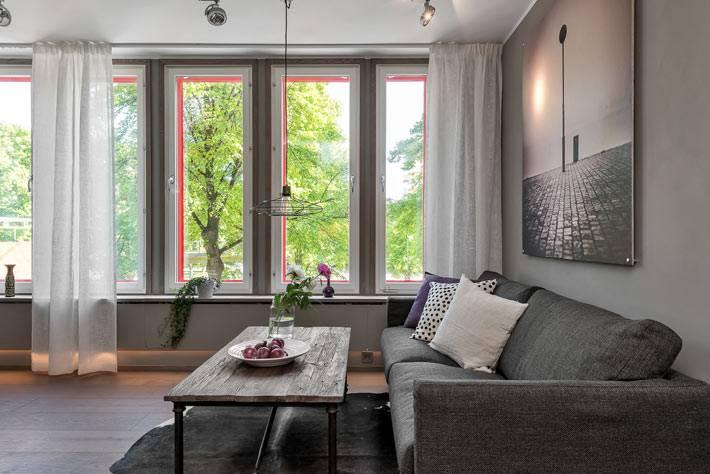 Серый диван в сером интерьере гостиной комнаты