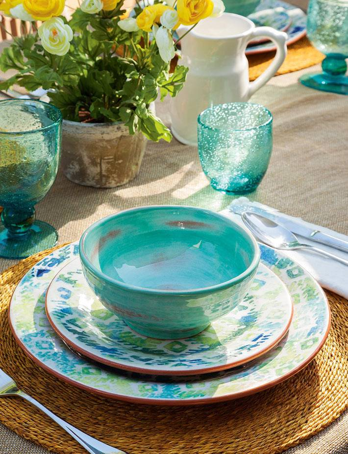 Красивая посуда для сервировке стола на летней террасе фото