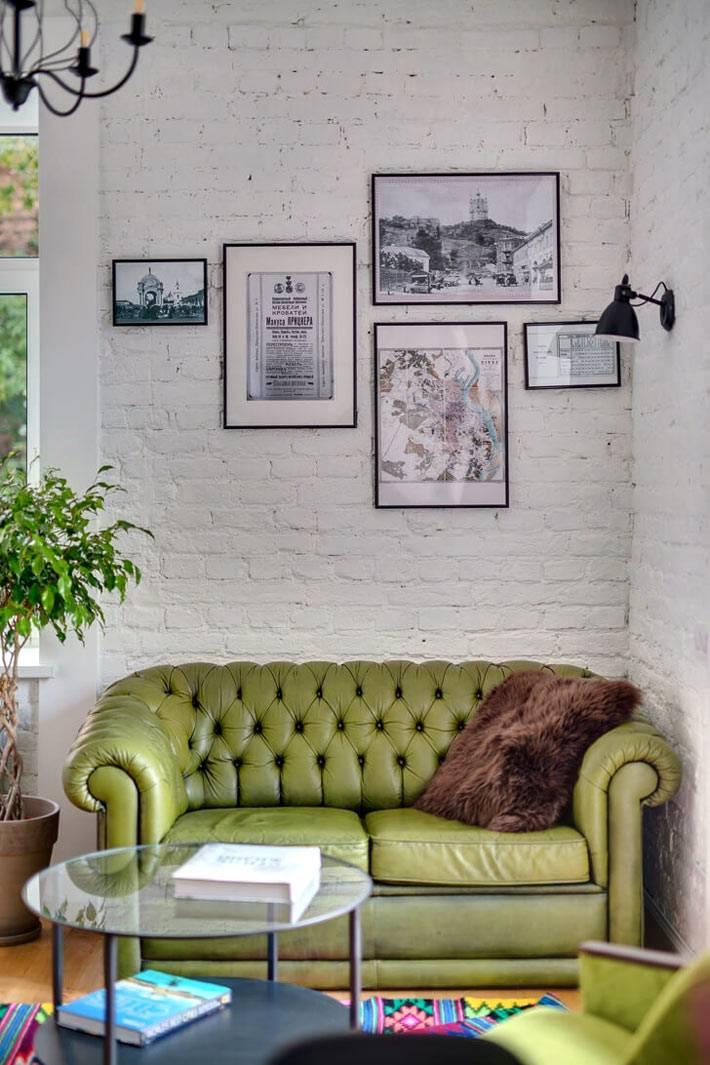 Белая кирпичная стена и зеленый диван как изюминка гостиной комнаты фото