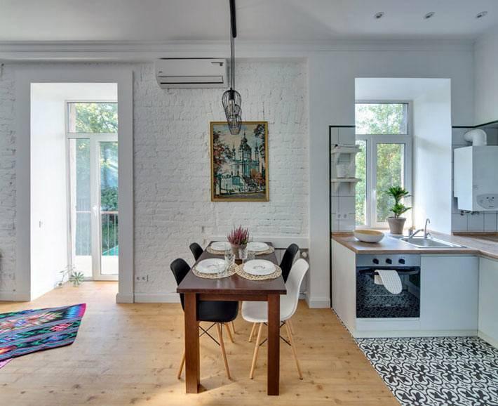 Квартира-студия с белыми кирпичными стенами и деревянным полом фото