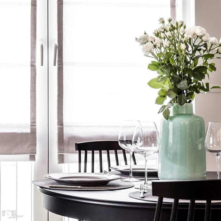 Красивая ваза с цветами на круглом обеденном столике фото