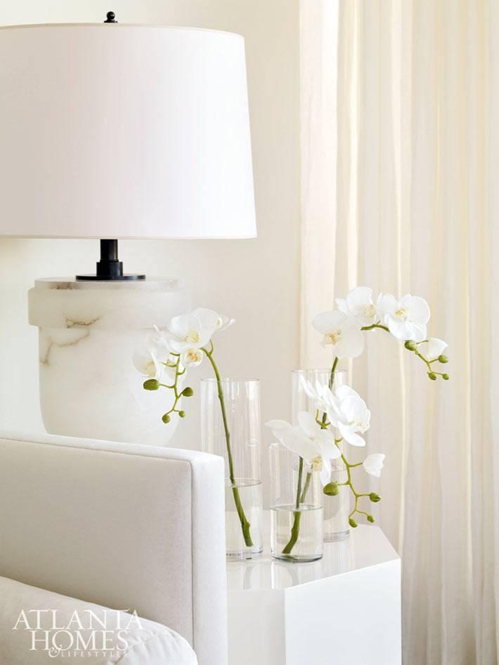 Белые орхидеи в белом интерьере гостиной фото