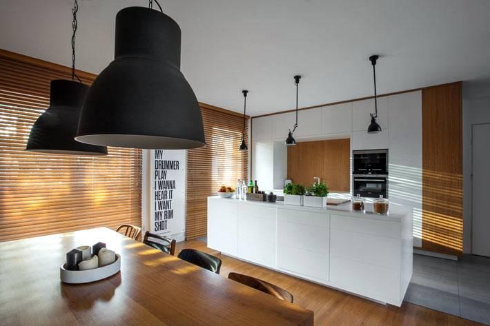 Стильные черные светильники над столовой зоной фото