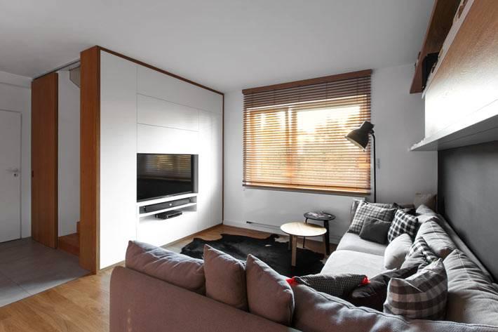 Угловой диван в гостиной зоне, совмещенной с кухне и столовой фото
