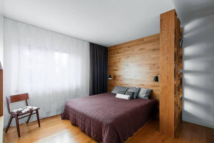 Стена в спальне возле изголовья кровати обшита натуральным деревом фото