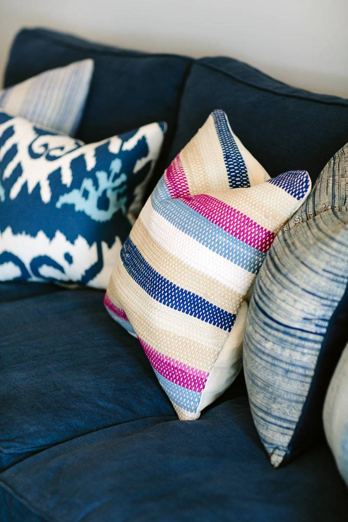Разные декоративные подушки на фоне синих диванов фото