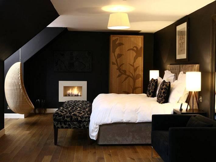 Уютная спальня в мансарде в черном цвете с подвесным креслом фото