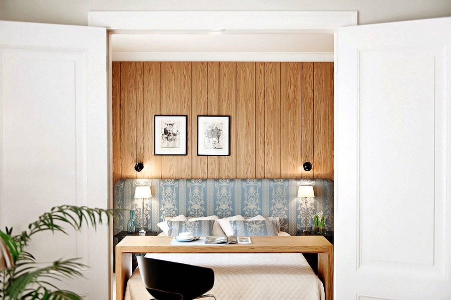 У изголовья кровати стена обшита деревянными панелями фото