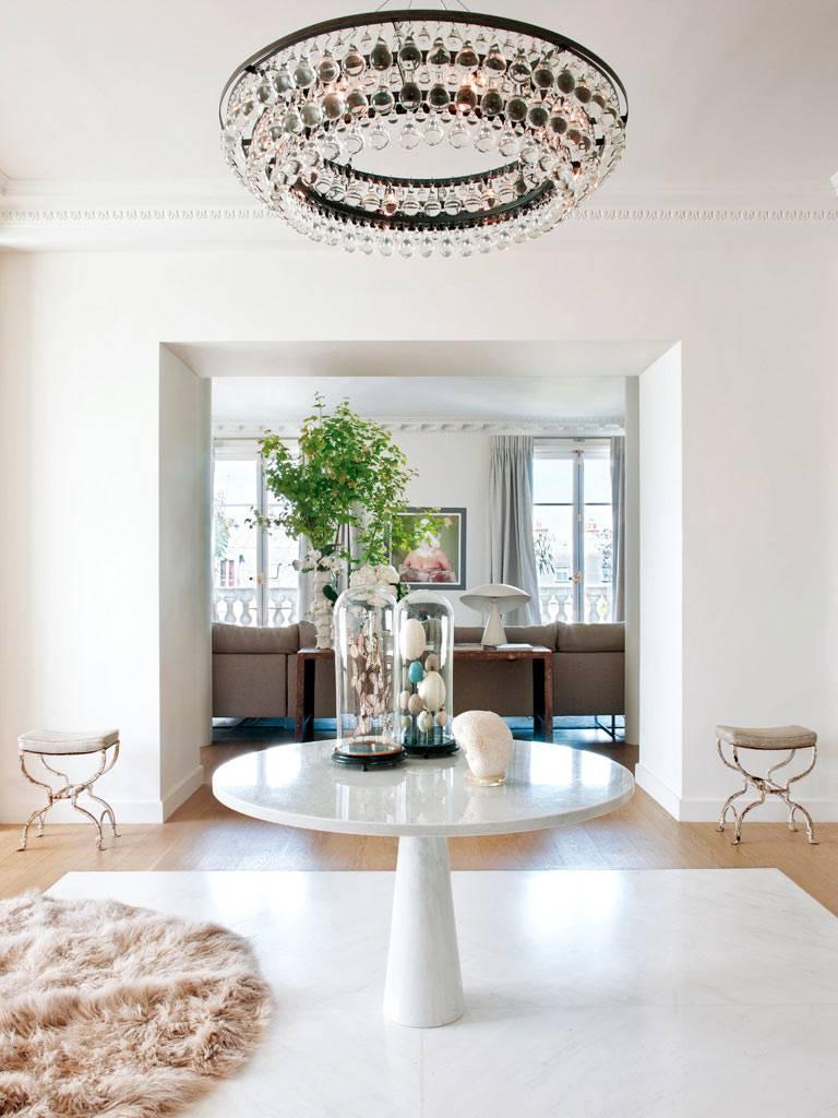 Мраморный стол в холле с красивой круглой люстрой фото