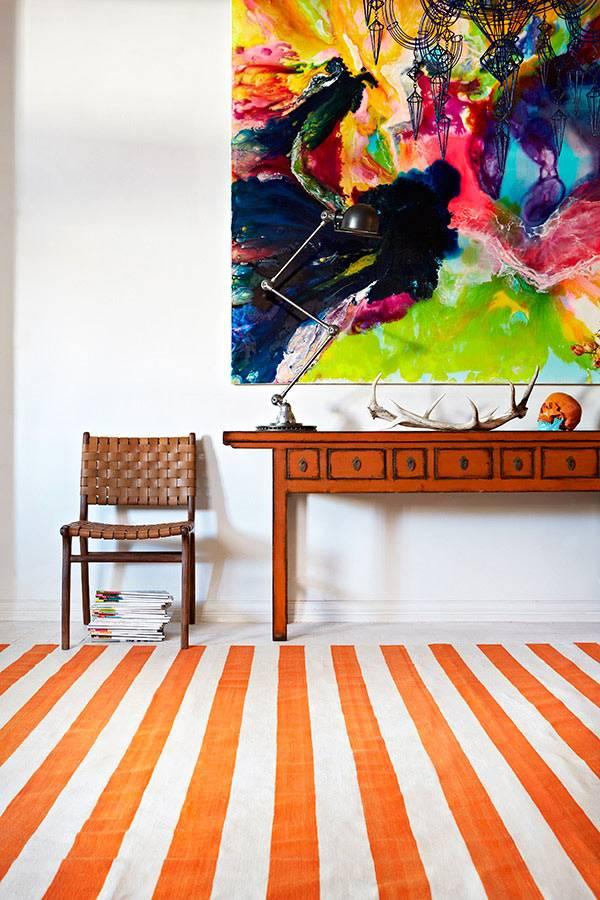 Яркий ковер с оранжевыми полосами в комнате фото