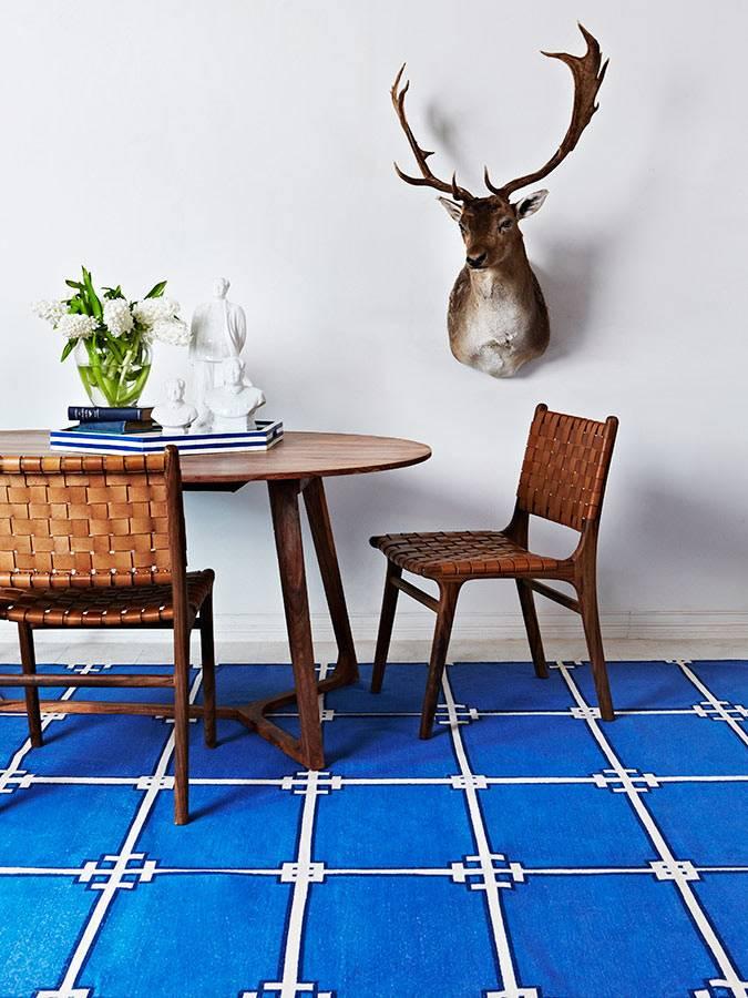 синий ковер освежиает комнату с белыми стенами фото