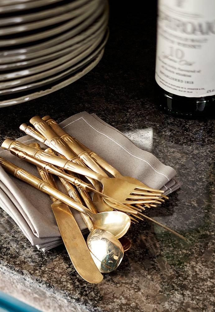 Шикарные столовые приборы зоотистого цвета на темной кухне фото
