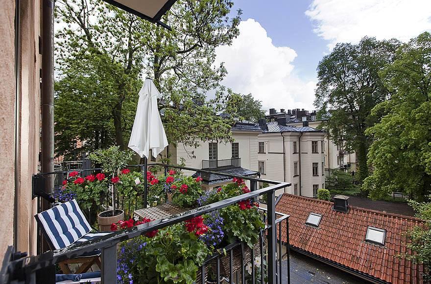 Красивый балкон для отдыха с цветами и удобными креслами фото
