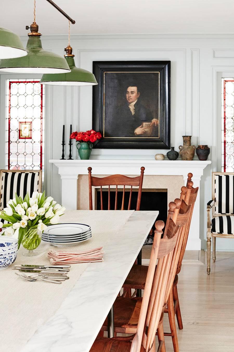 обеденный стол под современной люстрой с видом на старинную картину