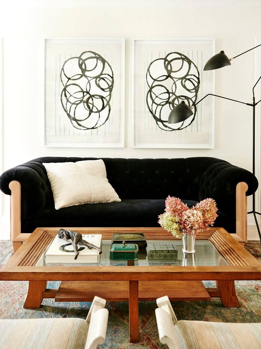 черный диван и абстрактные картины украшают интерьер гостиной комнаты