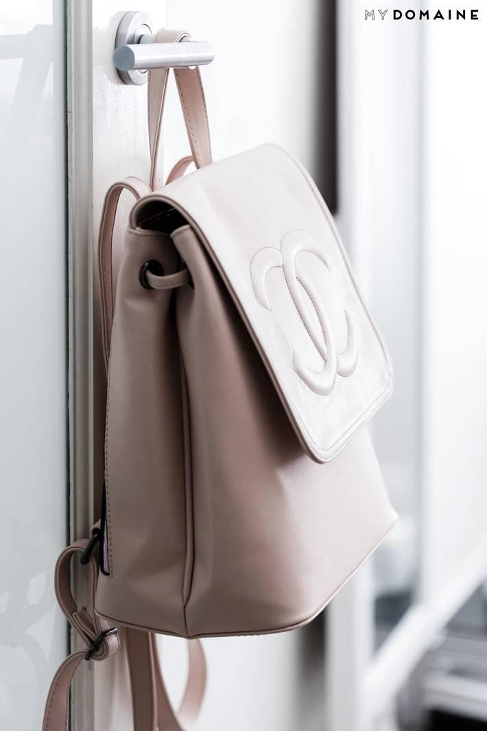рюкзак пудрового цвета на двери в комнате