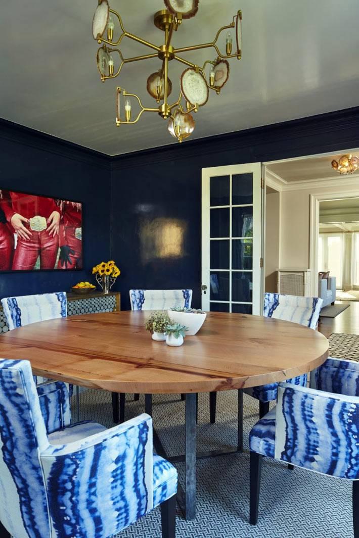 Дизайн столовой с темно-синими стенами и золотистой люстрой фото