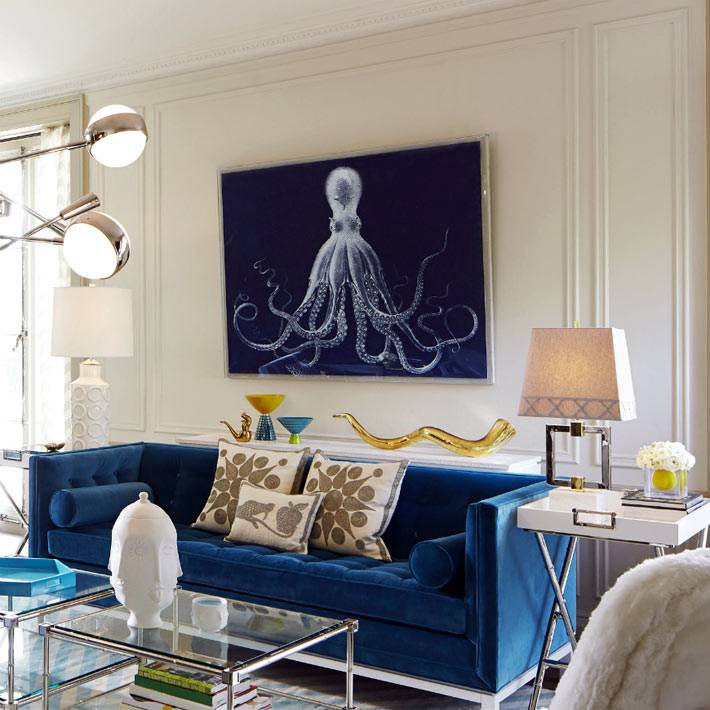 Синий диван в гостиной и два стеклянных столика фото