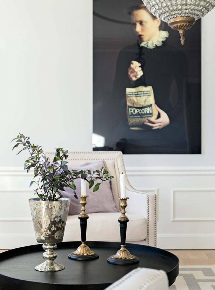 Черный круглый журнальный стол со свечами в гостиной фото