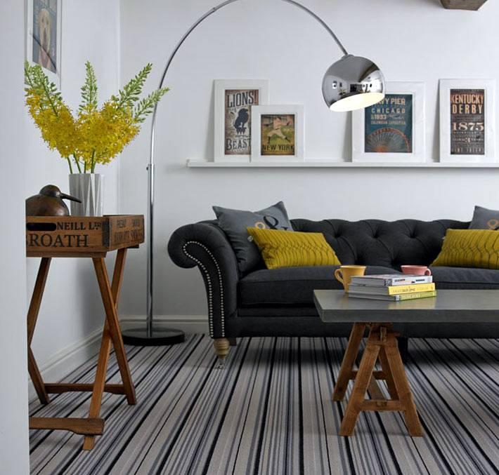 Серый диван сочетается с серыми полосками на полу фото