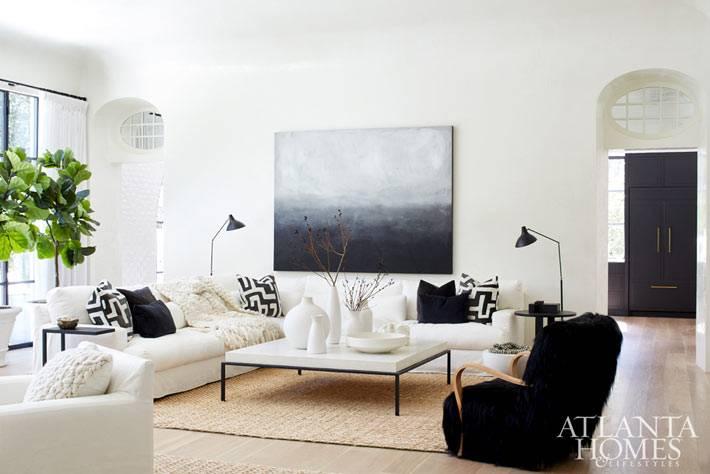 белые диваны на фоне белых стен разбавлены черными акцентами