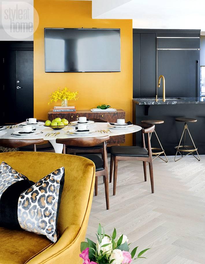 Черный телевизор на фоне желтой стены фото