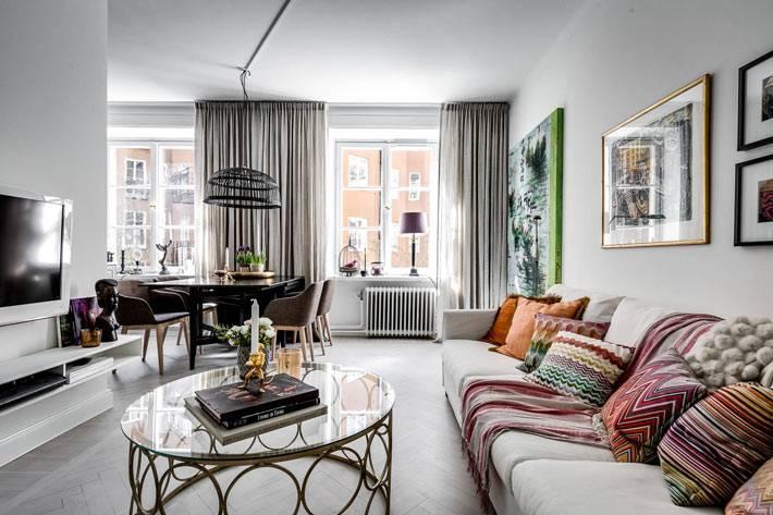 гостиная комната с яркими подушками и серыми шторами фото