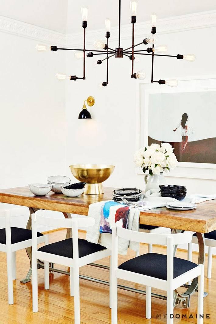 Деревянный обеденный стол с черно-белыми стульями и необычной люстрой