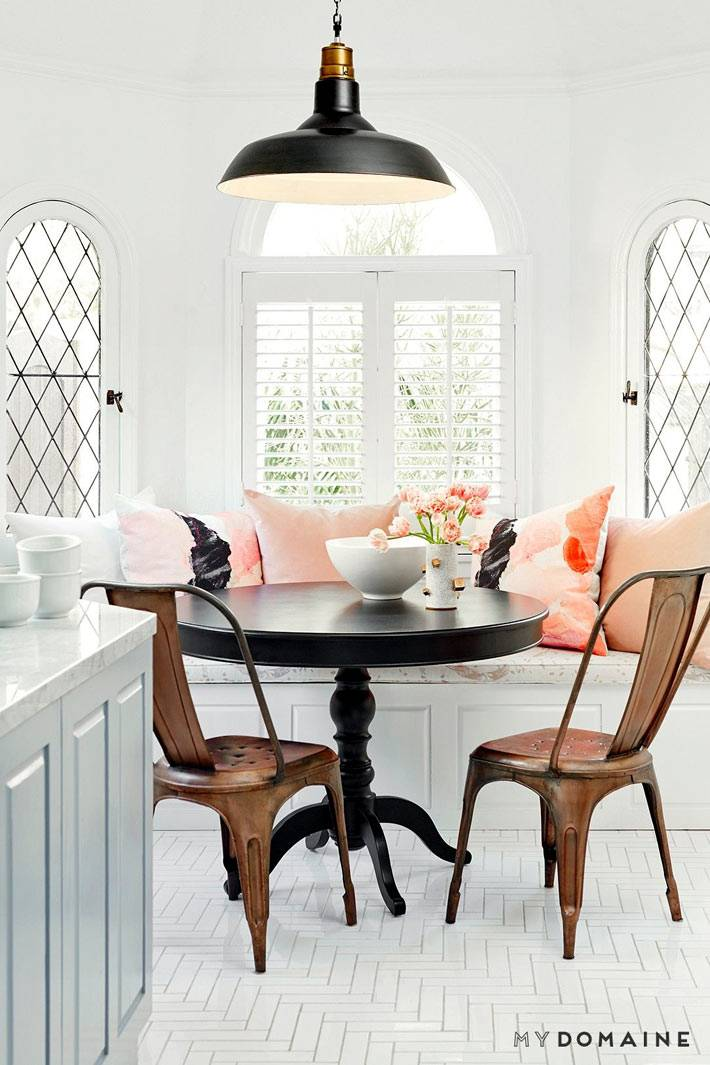 Светлое пространство с нежными розовыми подушками возле круглого стола