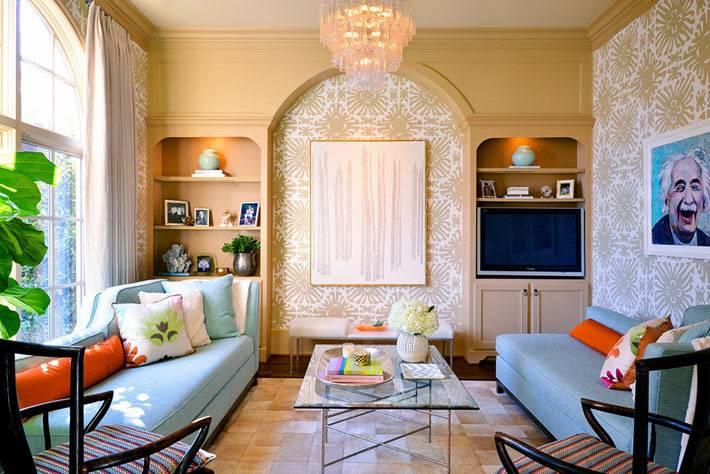 голубые диваны в гостиной комнате, арочный шкаф и портрет Эйнштейна на стене