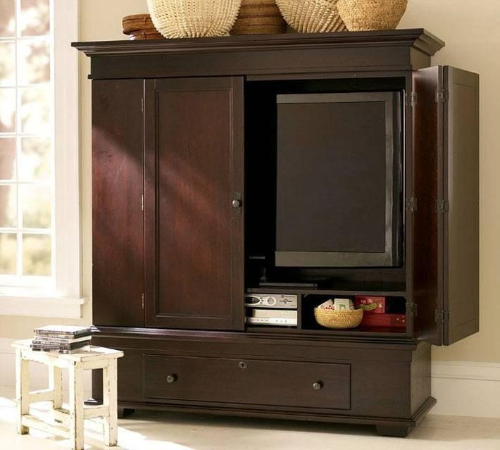 коричневый шкаф. в котором разместился телевизор и двд система