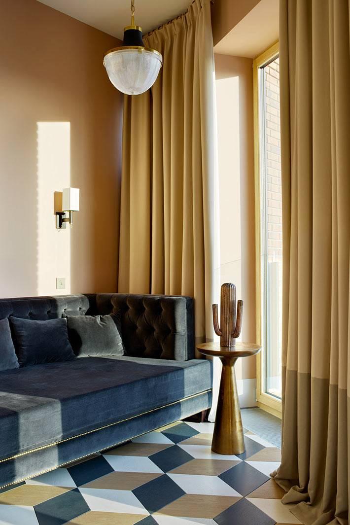 Бархатный диван синего цвета и песочные шторы фото
