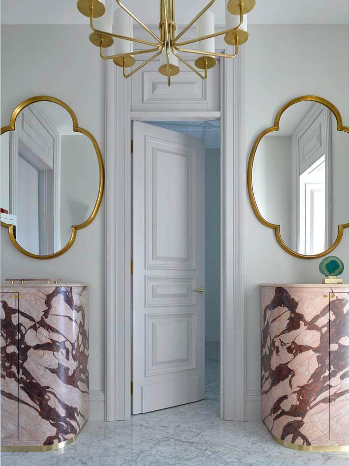 симметричные зеркала в прихожей комнате и мраморные тумбы