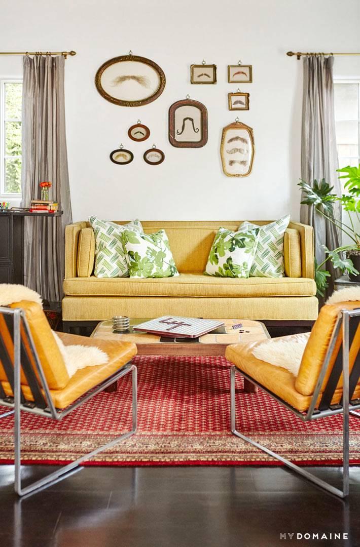 Мягкая мебель желтого цвета и рисунки усов в рамах на стене гостиной