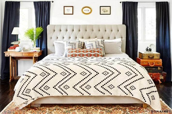 большая удобная кровать с мягким изголовьем в спальне
