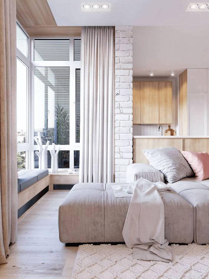 мягкий подоконник у окна и кирпичная кладка в квартире-студии