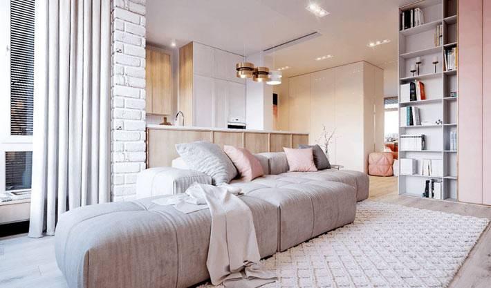 Квартира-студия в пастельных тонах с серым диваном